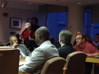 Jerry Belanger, far right, voices his opposition to plans for a new Detroit Red Wings arena as DEGC CEO George Jackson, far left, looks on.