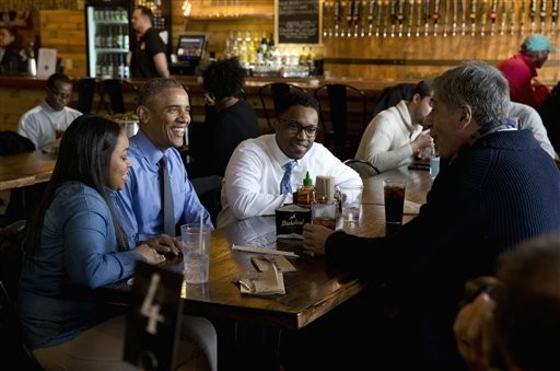 President Barack Obama has lunch at the Jolly Pumpkin Brewery in Detroit, Wednesday, Jan. 20, 2016, with Teana Dowdell, autoworker at the General Motors' Detroit-Hamtramck Assembly, left, Dr. Tolulope Sonuyi, Emergency medicine physician engaged with Detroit youth through violence prevention and intervention programs, part of Detroit's efforts around the My Brother's Keeper initiative, center, Detroit Mayor Mike Duggan, right, obscured, and Tom Kartsotis, Founder, Shinola. (AP Photo/Carolyn Kaster)