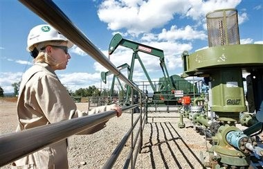 In this Aug. 26, 2009 file photo, Kourtney Hardwick, BP Florida operations manager, looks over a methane gas well site east of Bayfield, Colo.