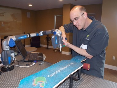 Diverse Dimensions owner Jeff Mass, using scanner ,makes a 3D scan of skateboard