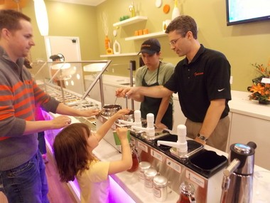 Peachwave Frozen Yogurt owner Boyd Feltman serving customers at the new downtown Holland store that opened on Thursday, April 10.