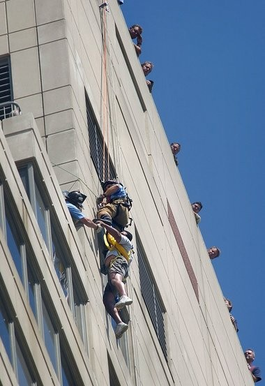 Firefighter Jeff Lysiak comes down from the top of the Plaza Towers building to help Moses Avila to safety in July 2003. Avila hung off the 32-story building for an hour before being rescued.