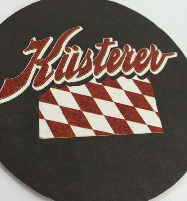 A Cedar Springs Brewing Company beer coaster bears the Kusterer logo.