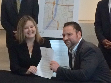Cheri Holman of the U.S. Green Building Council of West Michigan and Drew Coppess of 616 Development, sign the first charter for Grand Rapids 2030 District on Monday, Dec. 14.