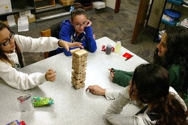 Clockwise from left, seventh-grader Jacqueline Velasco, eighth-grader Zulkia Falcon Martinez, seventh-grader Karen Ruiz Silva, and ninth-grader Daniela Ruiz Silva play Jenga during free time at a recent video shoot for the One Wyoming 1 on 1 mentor program.