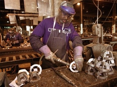 A worker completes a finishing grind to a part produced at Michigan Steel Inc. in 2002 when owner Vaughn Makary purchased the historic Muskegon foundry.