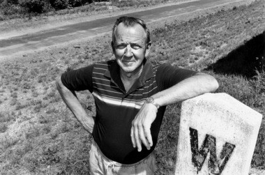 In this file photo, Bill Field rests on the stone whistle marker at the Shelby train depot, next to which runs the bike path he worked on developing.