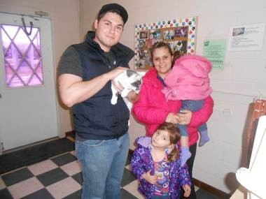 The White family members gather with their long-lost cat after recently being reunited with the pet. The reunion came about after the cat was scanned for a microchip that contained the owner's information.