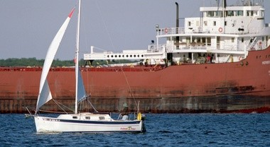 In this 2000 file photo, a sail boat is dwarfed by the Herbert C. Jackson freighter as it comes into port on the Muskegon Lake.