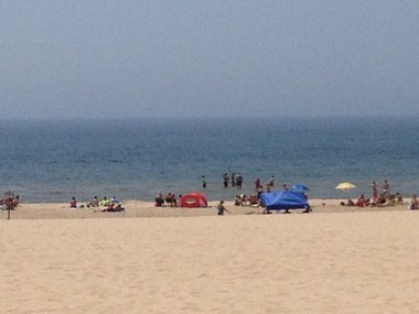 A small group of beach-goers test the water at the Muskegon State Park on Friday, July 5.