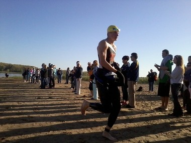 A runner begins to take off his wetsuit in preparation for the biking portion. Participants for the Bear Lake Triathlon had to move from the water to the bikes through sand going uphill.