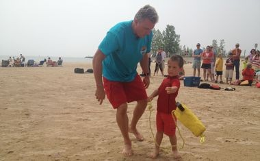 Bob Pratt, executive director of education for Great Lakes Surf Rescue Project, helps North Muskegon resident Bear VanDyke, 3, learn the proper technique to throw a flotation device in the event of a water emergency on Sunday, June 22, 2014, at Pere Marquette Beach in Muskegon.