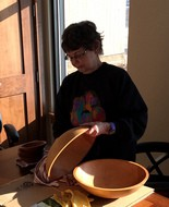 Volunteer Mimi Kunz of Whitehall rubs beeswax onto wooden bowls at Michigan's Heritage Park at Hilt's Landing in Muskegon County.