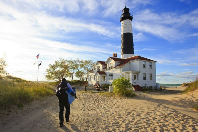 MLive Muskegon Chronicle reporter Brandon Champion walks with his over-night bag to Big Sable Point Light at Ludington State Park in Ludington, Mich. on September 29, 2015.