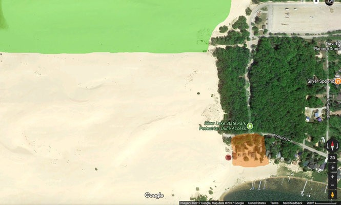 The green indicates a small portion of the Silver Lake State Park ORV course. The medium orange box is the 11 cottages in the current path of the dune and the red box marks the cottage that was swallowed by the dune in April. (Screenshot from Google Earth)