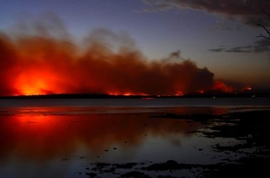 This photo provided by the New South Wales Rural Fire Service shows a fire near Sussex Inlet, Australia, on Jan. 12, 2013. Firefighters are battling scores of wildfires in southeastern Australia as authorities warned that hot, dry and windy conditions were combining to raise the threat to its highest alert level.