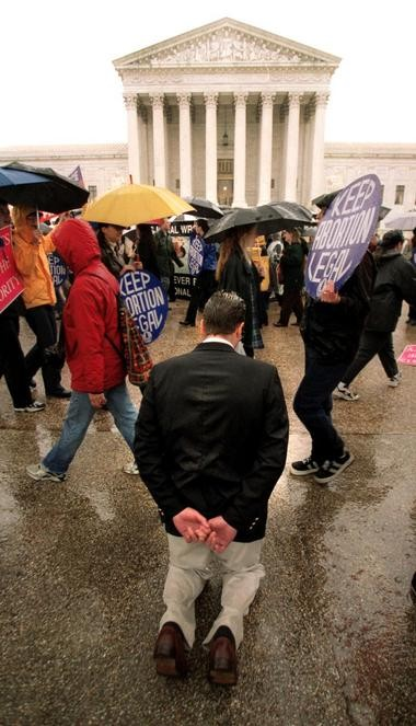 Dueling demonstrations outside the Supreme Court building are a common sight on the anniversary of the Roe v. Wade decision, which was issued Jan. 22, 1973.. A protester against abortion rights kneels in prayer outside the court while supporters march by in this 2000 photo. AP FILE PHOTO