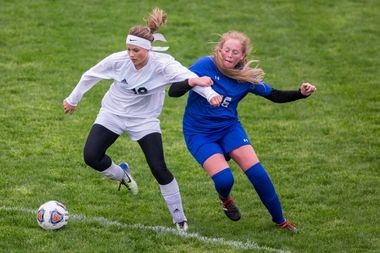 In this file photo, North Muskegon's Abby Grevel (18) shields Ravenna's Julie Breivik from the ball during a May 21, 2018 match in North Muskegon.