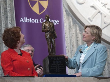 In March 2012, former Albion College President Donna Randall, left, and Susan Ford Bales unveil the President Gerald R. Ford maquette that will stand outside the office of Albion College's Gerald R. Ford Institute for Leadership in Public Policy and Service. Grand Rapids Mayor George Heartwell is in the background.