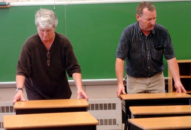 Former Harrington Elementary School custodians Vonnie Green, left, and Walter Moull set up desks in a classroom at the school. If Albion Public Schools officials choose to move to a K-8 model tonight, Harrington will close and all students will be taught at the high school.