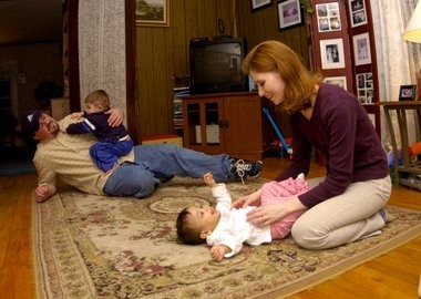 Stacy Fry plays with 1-year-old Ehlena while her husband, Brent, wrestles with Rhett, 2, in their Brooklyn home.