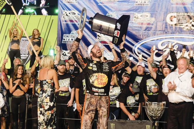 Brighton native Sherry Pollex stands in the background as longtime partner Martin Truex Jr. celebrates in Victory Lane after winning a NASCAR Cup Series auto race at Homestead-Miami Speedway in Homestead, Fla., Sunday, Nov. 19, 2017. (AP Photo/Gaston De Cardenas)