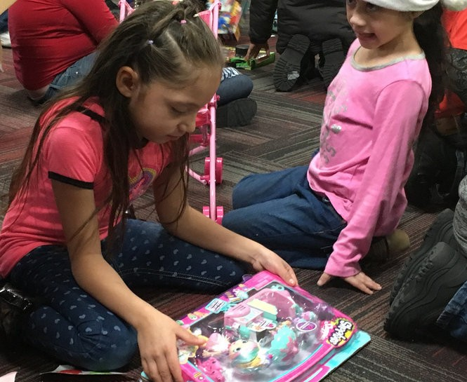 Alicia Cordova, 7, a second grader at Bennett Elementary School, looks at the gift she recieved Saturday, Dec. 9, during the Optimist Club of Jackson's holiday event, which provided gifts and activities for about 40 children.