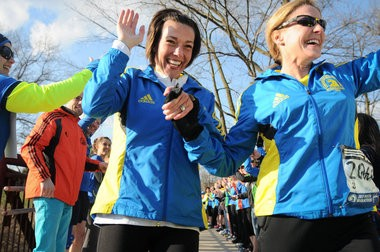 (left) Stephanie Schreiber-Bland, from Oxford, and Nancy Smith, from Shelby Township, cross the finish line of their Boston Marathon run hand-in-hand at Rochester Municipal Park surrounded by cheering runners, supporters and family Thursday, April 24. (Tanya Moutzalias | MLive.com)