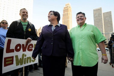 (left) Jayne Rowse and her partner April DeBoer, of Hazel Park, are surrounded by supporters rallying for the couple to win their lawsuit challenging the constitutionality of the state's adoption law and same-sex marriage ban outside the federal courthouse in Detroit Wednesday, Oct. 16. (Tanya Moutzalias | MLive.com)