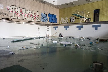 Katie Bailey | MLive.com The pool at Southwestern High School has been mostly drained of water, but not entirely, leaving a skating rink filled with debris, included trash, a microwave and a desk chair, Feb. 18, 2014. The school, built in 1915, was closed in 2012 because of declining numbers. The sprawling 245,000-square-foot school is now pending sale by the Detroit Public School System, despite it being gutted by scrappers for anything and everything valuable.