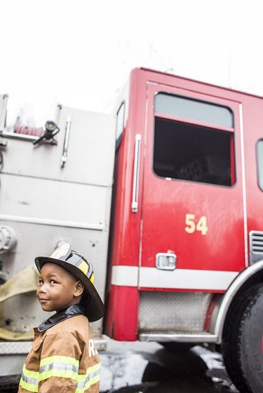 Katie Bailey | MLive.com Tyren Johnson, 3, steals a look at his grandmother after arriving at Detroit Fire Department Ladder 54 by firetruck, Tuesday, April 29, 2014. Tyren, a heart transplant survivor, said all he wanted was to be a firefighter. The Make-A-Wish Foundation partnered with the fire department to make that come true on World Wish Day. Tyren rode in a truck, sprayed a hose, received awards and enjoyed a lunch inside the firehouse.