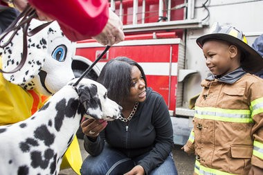 Katie Bailey | MLive.com Tyren Johnson, 3, meets Vegas, a Dalmatian competition dog, after arriving at Detroit Fire Department Ladder 54 by firetruck, Tuesday, April 29, 2014. Tyren, a heart transplant survivor, said all he wanted was to be a firefighter. The Make-A-Wish Foundation partnered with the fire department to make that come true on World Wish Day. Tyren rode in a truck, sprayed a hose, received awards and enjoyed a lunch inside the firehouse.
