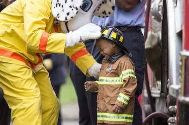 Katie Bailey | MLive.com Detroit Fire Department mascot Patches nuzzles 3-year-old Tyren Johnson at Ladder 54 during Tyren's firefighter for a day event, Tuesday, April 29, 2014. Tyren, a heart transplant survivor, said all he wanted was to be a firefighter, and the Make-A-Wish Foundation partnered with the fire department to make that come true on World Wish Day. Tyren rode in a truck, sprayed a hose, received awards and enjoyed a lunch inside the firehouse.