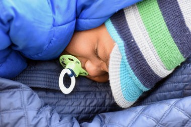 """Angel Hempfield, of West Bloomfield, holds her two year-old son Jackson who sheds a tear during a staged """"die-in"""" in Campus Martius Park in downtown Detroit Thursday afternoon in a rally over the grand jury decision to not indict the NY Police officer who killed Eric Garner. (Tanya Moutzalias 