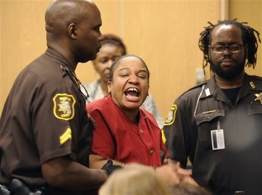 Mitchelle Blair is lead out of the court room by Wayne County Sheriff deputies after an outburst of screaming during a custody hearing before Wayne County Circuit Judge Edward Joseph on Thursday, June 4, 2015 in Detroit. Blair was temporarily removed during the custody trial to settle her parental rights to her surviving 8-year-old son and 17-year-old daughter. She was arrested March 24 after court deputies carrying out an eviction at her apartment found the bodies of Stoni Blair, 13, and Stephen Berry, 9, in a deep freezer. Police believe they died months apart in 2012 and 2013. (Clarence Tabb Jr./Detroit News via AP)