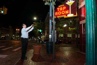 """Statewide Mlive entertainment reporter John """"Gonzo"""" Gonzalez takes a picture of the outside of The Tap Room in Ypsilanti, Mich. on Monday, September 15, 2014. Tyler Stabile 