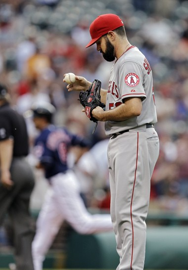 Los Angeles Angels starting pitcher Matt Shoemaker inspects a new baseball after giving up a solo home run to Cleveland Indians' Lonnie Chisenhall in the fourth inning of a baseball game Tuesday, June 17, 2014, in Cleveland.