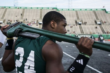 """EMU senior defensive back Michael Denson holds the 65 lb. wrench in """"The Factory"""" at the EMU vs. Morgan State football game on Saturday, August 30, 2014, at Rynearson Stadium in Ypsilanti. Katie McLean 