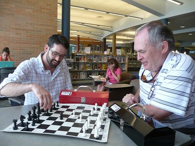 William and Charles Gallmeyer play a game of chess with their unique Tool Chess pieces at the East Grand Rapids library.