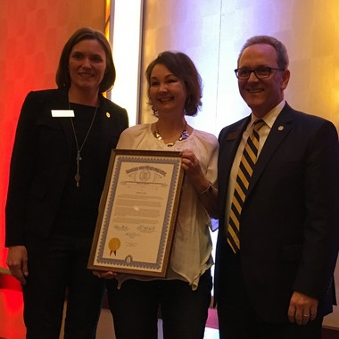 Successful East Grand Rapids We the People coach Janice yates receives a proclamation from state representatives Winni Brinks and Chris Afendoulis at a recent auction held to raise funds to send her team to national finals.