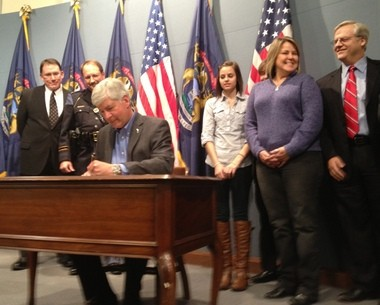 Gov. Rick Snyder signs Kelsey's Law Tuesday, Jan. 8, banning cellphone use by teen drivers. Behind him, Bonnie Raffaele, mother of Kelsey, smiles at Sen. Howard Walker, who sponsored the bill.