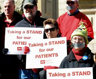 Protesters gather for the UAW silent protest Thursday March 28, 2013, on the Capitol steps in Lansing, Mich., to protest the new right-to-work law. Republican Gov. Rick Snyder said a right-to-work law that took effect Thursday is a milestone that will bring jobs to Michigan, while protesters promised to exact revenge at the polls for the contentious measure Snyder signed in December. (AP Photo/The State Journal,Greg DeRuiter )