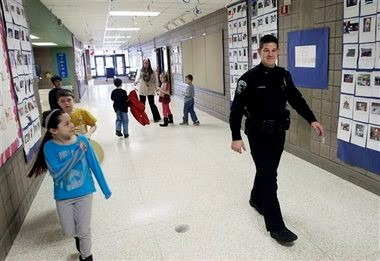 In this Feb. 21, 2013 file photo, a young girl waves at police officer Jeff Strack as he walks the hallway of Jordan Elementary School in Jordan, Minn., a small town that decided to place satellite police offices in its public schools. Gun rights supporters in Jordan had made a push to arm school personnel after the Connecticut school shooting four months ago, but those proposals have stalled in many other states.