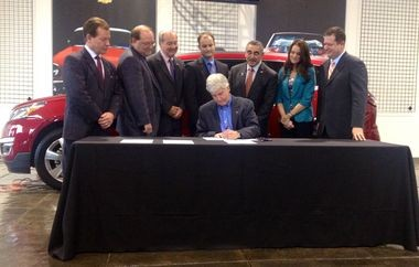 """Michigan Gov. Rick Snyder signs """"sales tax on the difference"""" legislation at Shaheen Chevrolet in Lansing on November 6, 2013."""