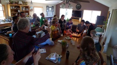 Elijah Courser, 13, prepares to blow out the candles on his birthday cake at a regular Sunday gathering of his large extended family in Lapeer. (Bridge photo by Nancy Derringer)