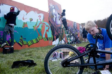 Aaron Schmidt, 13, of Flint, Mich., borrows a can of spray paint to paint his bicycle while graffiti artists from as far as Chicago work on a 336 foot wall at Bring It Fest in Kearsley Park in Flint Sept. 18, 2011. Graffiti is one example of an art form that was at first dismissed by the art world but is now gaining acceptance.