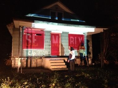 """Volunteers paint the word """"assembly"""" on a vacant house in Flint as part of the Flint Public Art Project's October, 2014, art parade."""