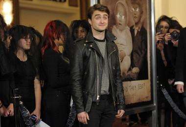 """Daniel Radcliffe, a cast member in the supernatural thriller """"The Woman in Black,"""" poses amongst black-clad fans at the premiere of the film in Los Angeles, Thursday, Feb. 2, 2012. (AP Photo/Chris Pizzello)"""