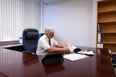 Michael Brown goes over paperwork to be completed in his cleaned out office during his last day as Flint's emergency manager in August 2012.