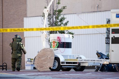 In this 2012 file photo, a bomb squad law enforcement official responds to a suspicious bag left on Saginaw Street, temporarily closing the block between West 2nd and West 3rd streets in Flint. The scare was unfounded.